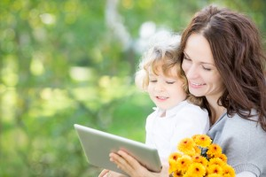 Happy family with bouquet of spring flowers using tablet PC outdoors. Mothers day celebration concept