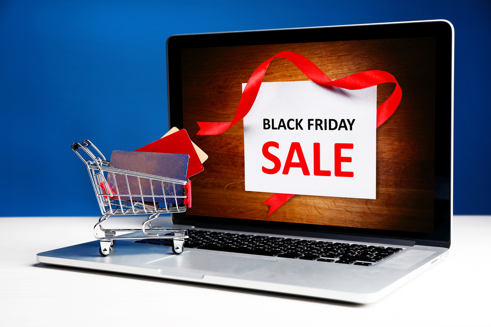 Credit cards in shopping cart and laptop, Black Friday Sale concept