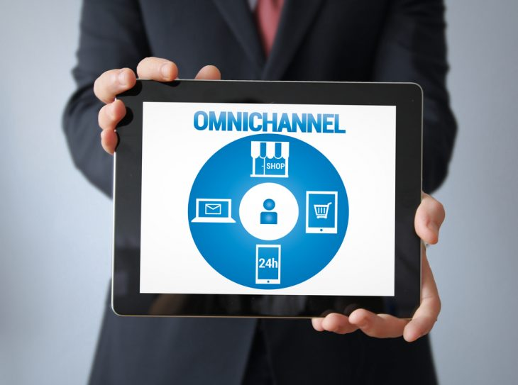 E-commerce Concept: Businessman with omnichannel on the screen. All graphics are made up.